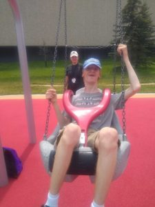 a teenage boy swings in a specialty swing