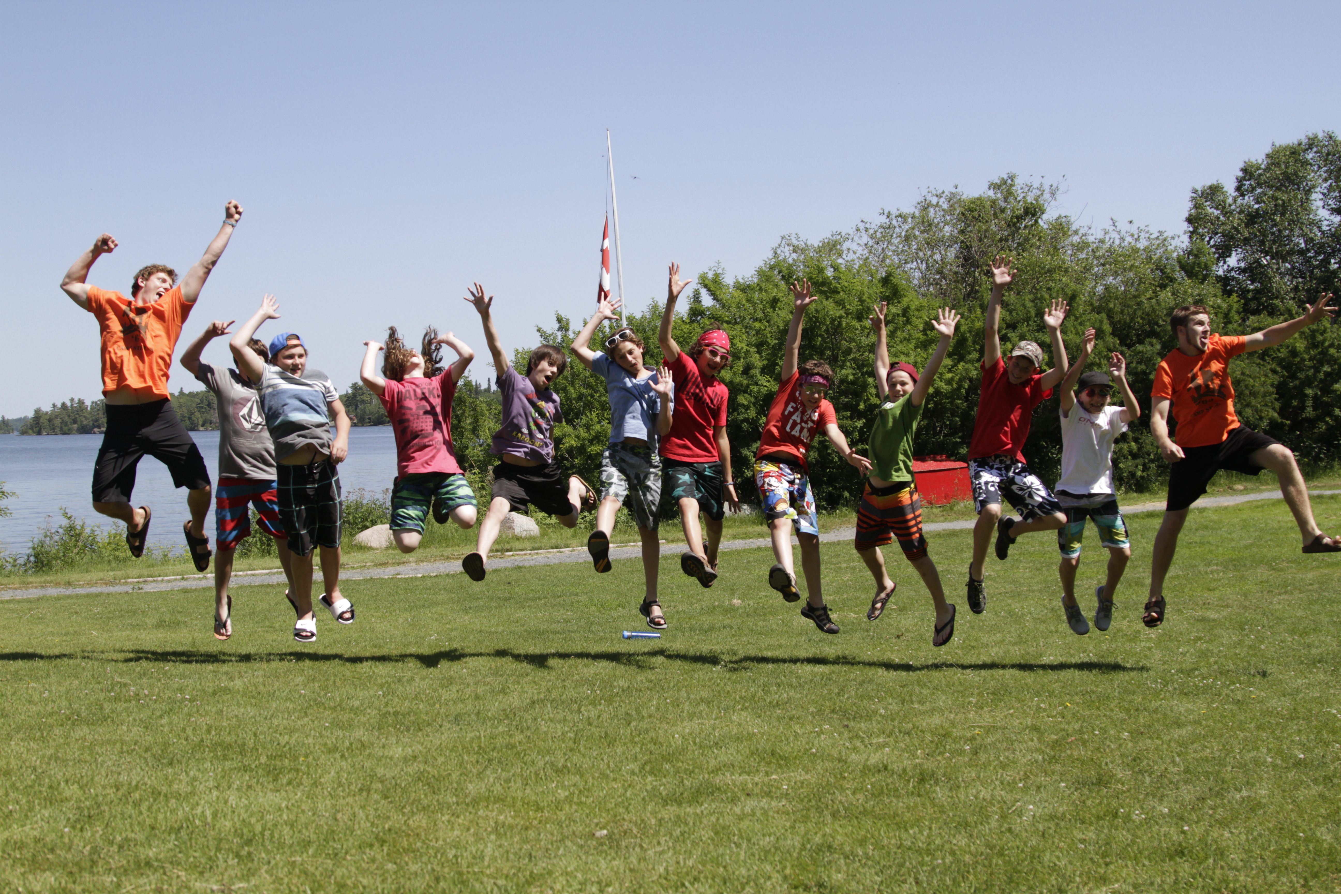 A group of kids jump in the air in excitement, surrounded by blue sky