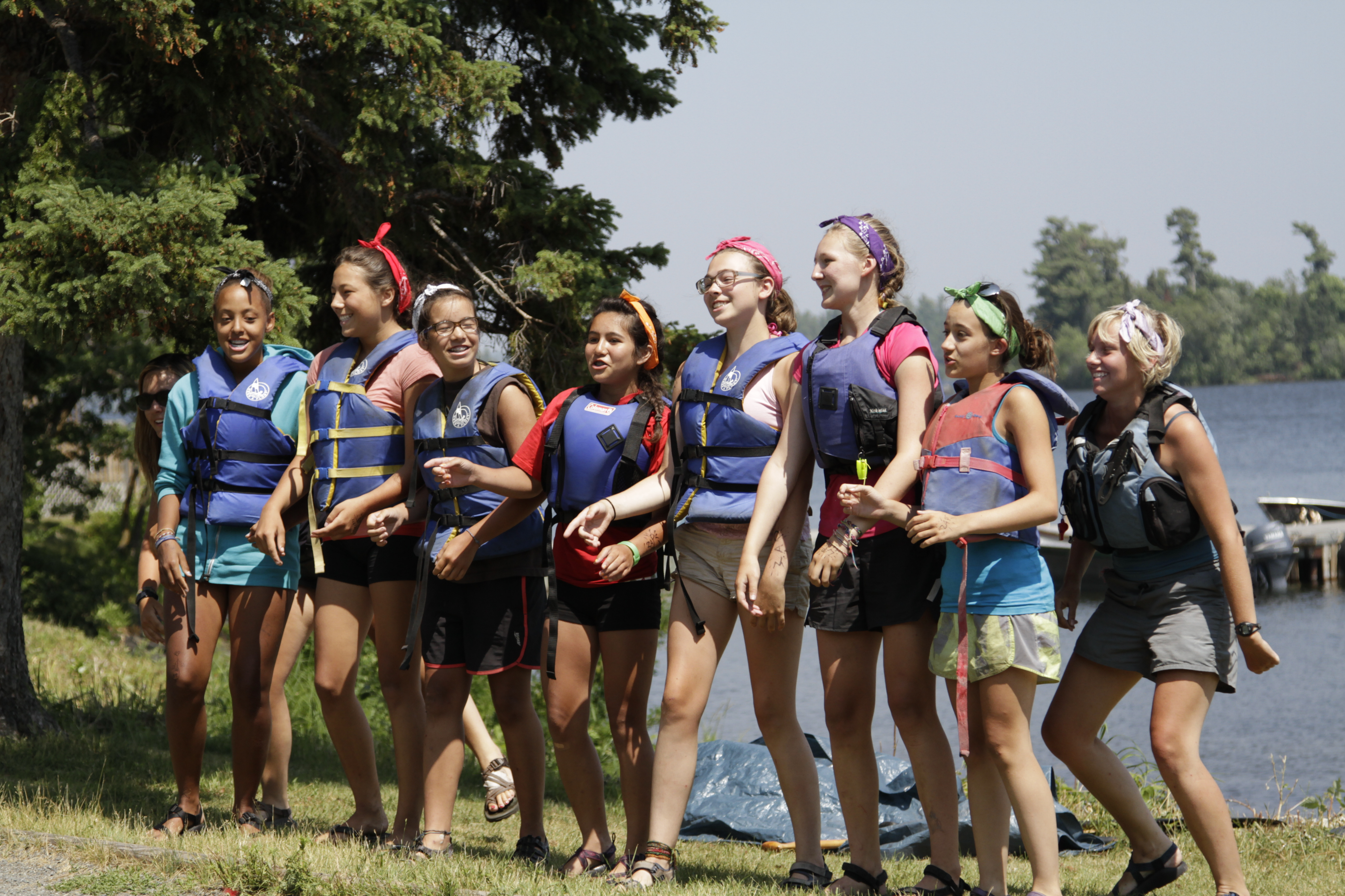 A group of girls in life jackets stand on the shores of Lake of the Woods
