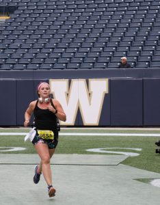 a woman runs through a football field